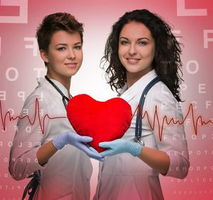 Two woman doctor holding a red heart on red Ophthalmic table background